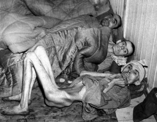 Three starved and maltreated prisoners of war huddle together at the Buchenwald concentration camp near Weimar, Germany, in April 1945, just before American troops liberated the camp. (AP)