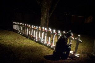Frank Kulick adjusts a display of wooden crosses and a Jewish Star of David representing the victims of the Sandy Hook Elementary School shooting, on his front lawn on Dec. 17, 2012, in Newtown, Conn. (AP)