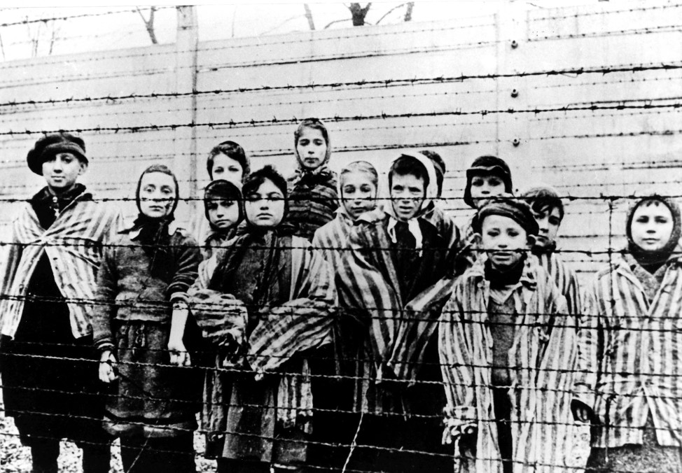This photo tsken in January 1945, after the liberation by the Soviet army, shows a group of children behind barbed wire fencing in the Auschwitz Nazi concentration camp. (AP)