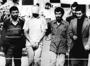 In this Nov. 9, 1979, file photo, a blindfolded  American hostage is paraded outside the U.S. embassy in Tehran.