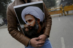 A Shi'ite Muslim man holds a picture of cleric Sheikh Nimr al-Nimr during a protest against the execution of Nimr, who was executed along with others in Saudi Arabia, in front of Saudi Arabia embassy in New Delhi on Jan. 4, 2016. (Reuters)