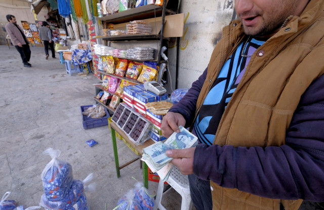 An Iranian shopkeeper counts money as he waits for customers in front of his shop in northern Tehran on Jan. 16, 2016. (Reuters)