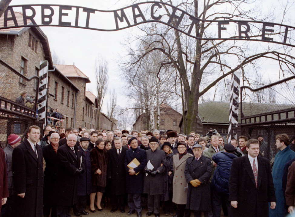 Officials and representatives mourn in silence at the main gate of the Auschwitz concentration camp to mark the 50th anniversary of its liberation on January 27, 1995. (Reuters)