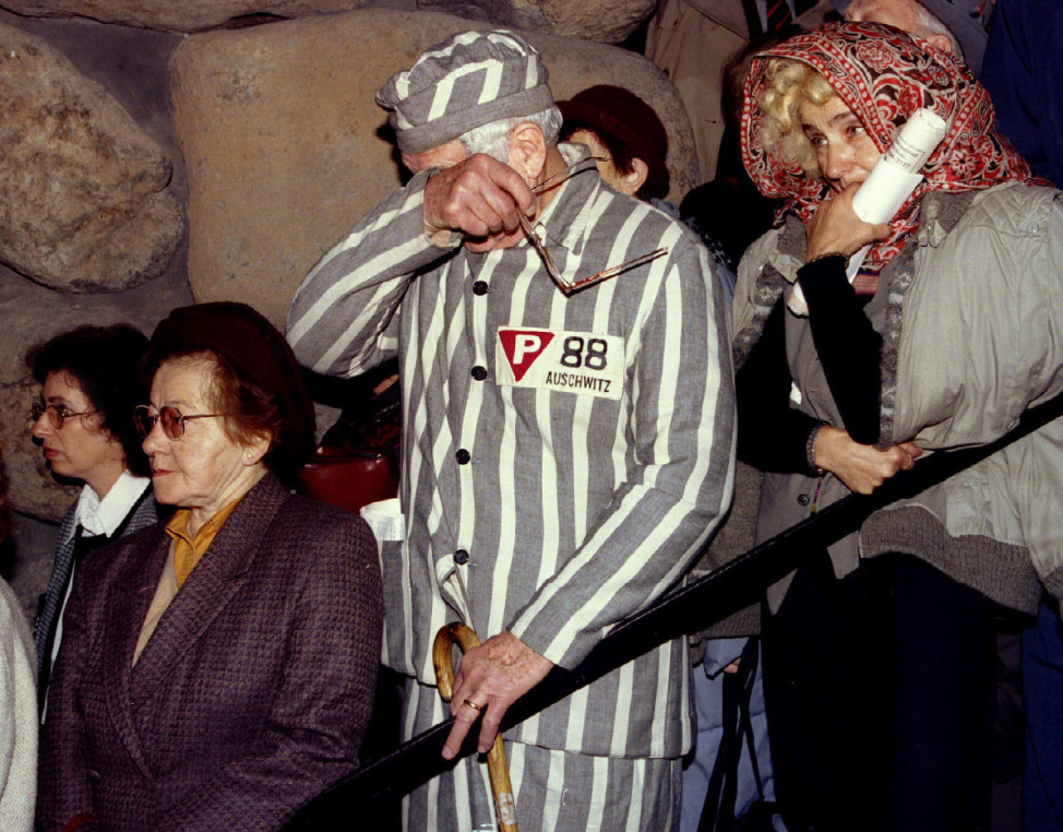 Auschwitz survivor Sigmund Sobolewski, 72, wearing concentration camp clothing, wipes away his tears during a commemorative service at the Yad Vashem Holocaust Memorial, marking the 50th anniversary of the liberation of the Nazi death camp in 1995. (Reuters)