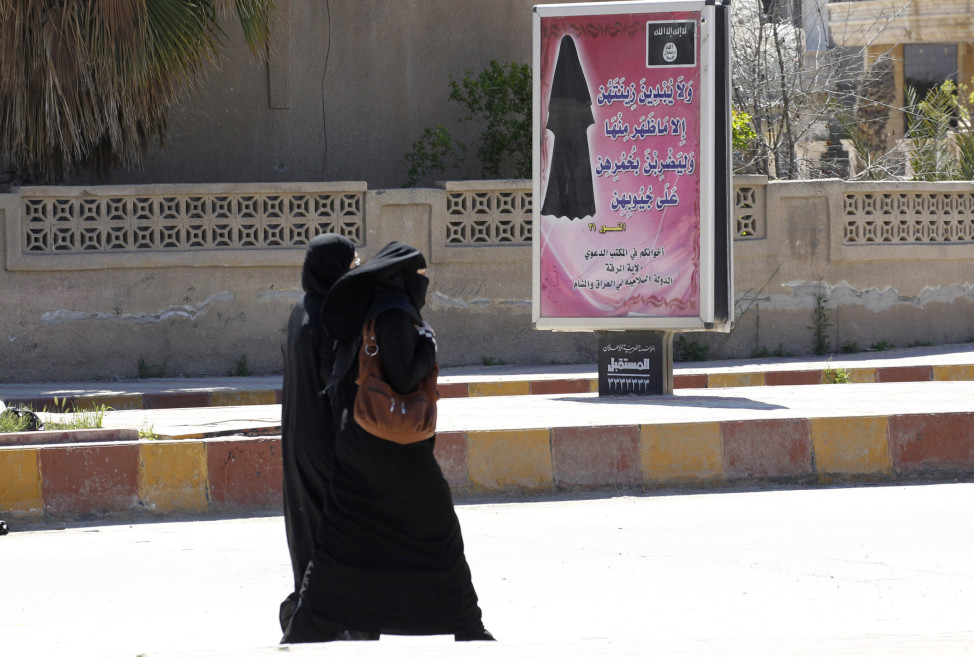 Veiled women walk past a billboard inscribed with a verse from Koran, urging women to wear a hijab in the northern province of Raqqa on Mar. 31, 2014.