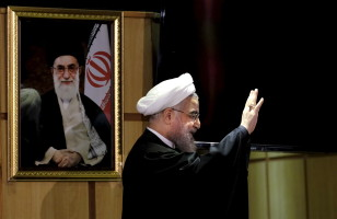Iranian President Hassan Rouhani waves as he stands next to a portrait of Iran's Supreme Leader Ayatollah Ali Khamenei at interior ministry in Tehran December 21, 2015. (Reuters)
