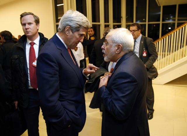 Secretary of State John Kerry talks with Iranian Foreign Minister Mohammad Javad Zarif, right, after the International Atomic Energy Agency verified that Iran has met all conditions under the nuclear deal on Jan 16, 2015 in Vienna. (AP)