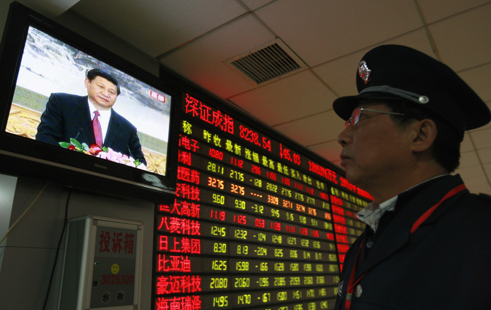 A security guard watches a screen showing Xi Jinping, the newly-elected General Secretary of the Central Committee of the Communist Party of China, holding a news conference in front of an electronic board showing stock information at a brokerage house in  Anhui province, China in this Nov. 15, 2012 file photo (Reuters)