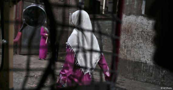 An Egyptian woman seen from a motorized rickshaw walks on a street, near the home of a 13-year old girl who died undergoing the procedure of female genital mutilation committed near Cairo, Egypt.(AP)