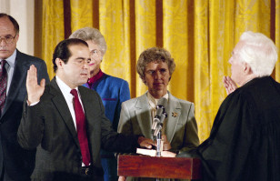 Retiring Chief Justice Warren Burger, right, administers an oath to Associate Justice Antonin Scalia, as Scalia's wife, Maureen, holds the bible in the East Room of White House in Sept. 1986 (AP/file)