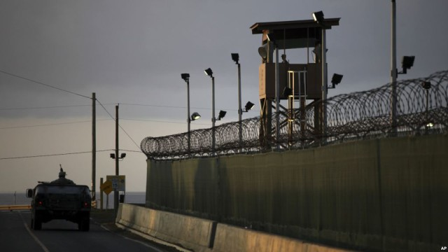 FILE - A U.S. soldier stands in the turret of a vehicle with a machine gun, left, as a guard looks out from a tower at the Guantanamo Bay prison in Cuba, March 30, 2010