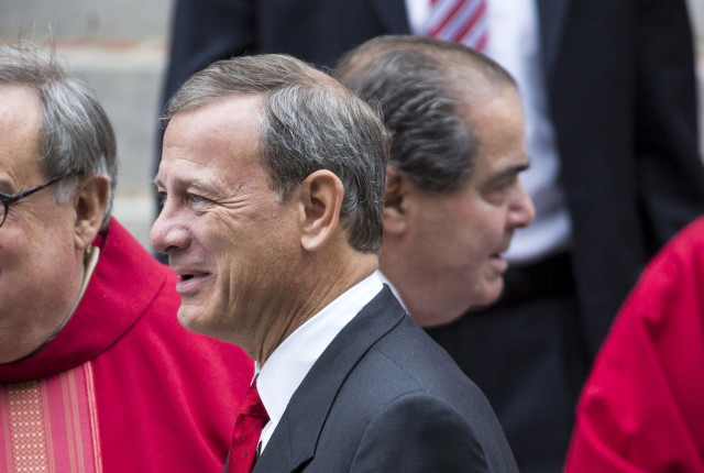 Supreme Court Justice John Roberts (centre L) passes by Associate Justice Antonin Scalia (centre R) as they depart from St. Matthews Catholic Church after attending the 63rd annual Red Mass on the Sunday before the U.S. Supreme Court's new term opens in Washington, Oct.. 4, 2015. REUTERS