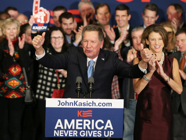 Republican presidential candidate John Kasich beams at the crowd with his wife Karen (R) at a presidential primary night rally in Concord, New Hampshire on Feb. 9, 2016.