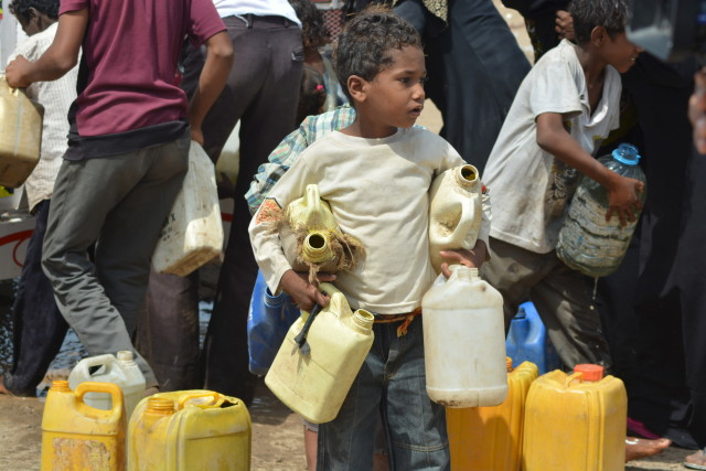 A boy carries jerry cans to fill from a water tanker truck in in Yemen's Red Sea city of Houdieda on Feb.15, 2016. (Reuters)
