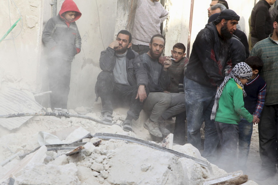 People sit on the rubble of a damaged building after airstrikes by pro-Syrian government forces in the rebel held city of Aleppo, Syria on Feb. 14, 2016. REUTERS