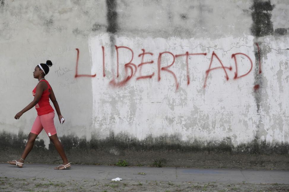 "A young woman walks near graffiti that reads ""Freedom"" in Havana, Cuba on Feb. 21, 2016. (AP)"