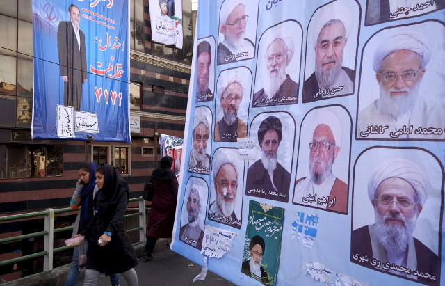 Women walk past electoral posters for the upcoming elections in central Tehran Feb. 24, 2016. REUTERS