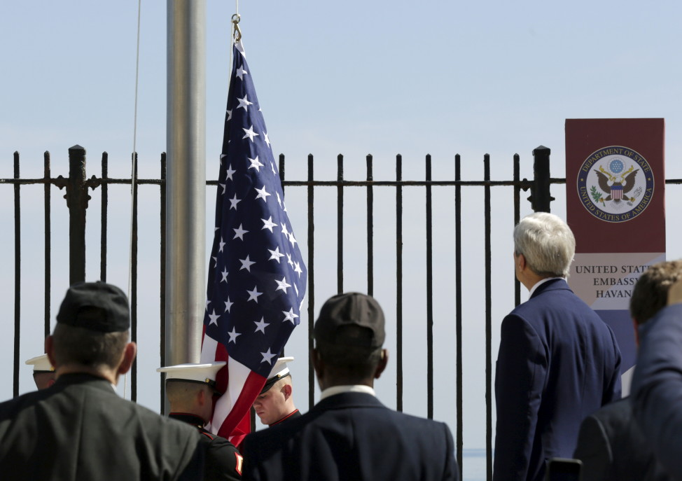 U.S. Marines raise the U.S. flag while being watched over by U.S. Secretary of State John Kerry at the U.S. embassy in Havan