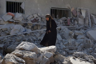 A woman walks through rubble after airstrikes by pro-Syrian government forces in the rebel held town of Dael in Deraa, Syria on Feb.12, 2016. (Reuters)