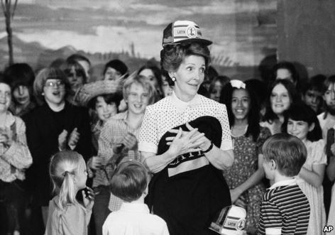 First lady Nancy Regan models a school cap and holds a school shirt presented to her during her visit to Chicago's Latin School, May 14, 1982.