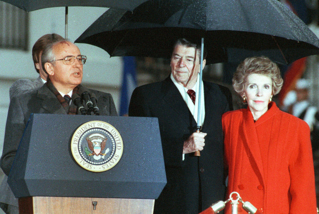Former U.S. President Ronald Reagan (C) and his wife Nancy listen to former Soviet leader Mikhail Gorbachev (L) speak during Gorbachev's departure ceremony at the White House in Washington in this December 10, 1987 file photo. (Reuters)