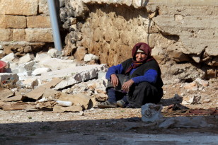 A woman rests near rubble on the ground in the town of Darat Izza in Aleppo, Syria on Feb. 28, 2016. (Reuters)