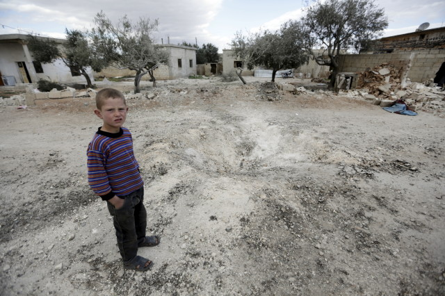 A boy stands near a hole in the ground after a shell fell in the rebel-held town of Jarjanaz, southern Idlib countryside, Syria March 5, 2016. (Reuters)