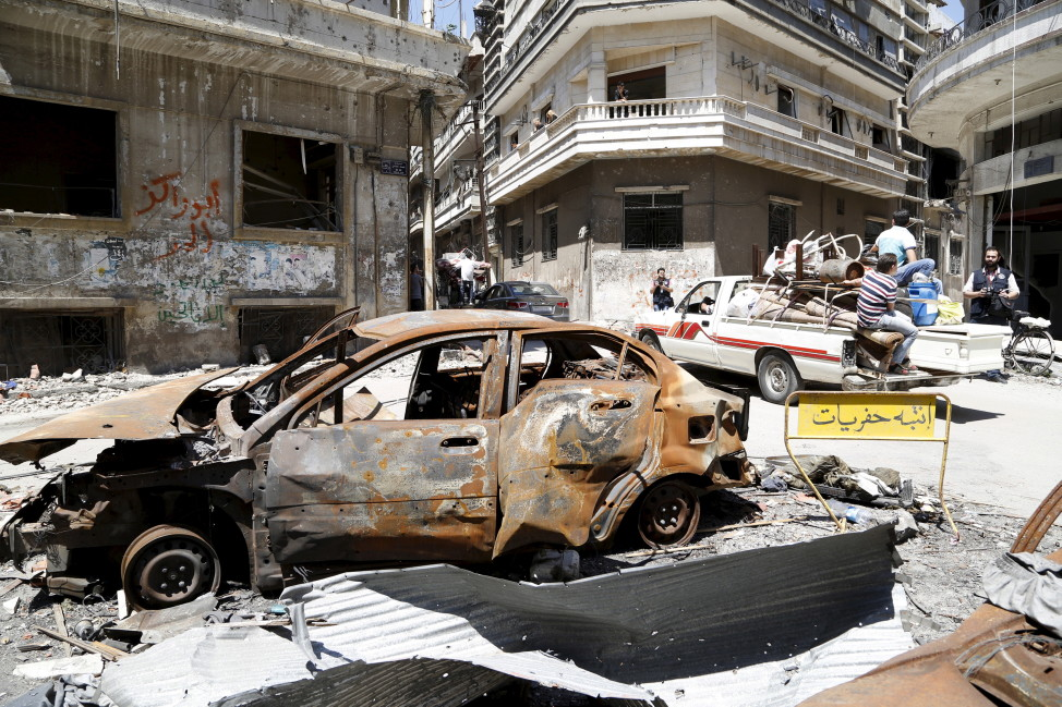 A truck drives past a vehicle, damaged during the Syrian conflict between government forces and rebels, Homs, Syria May 13, 2014. (Reuters)