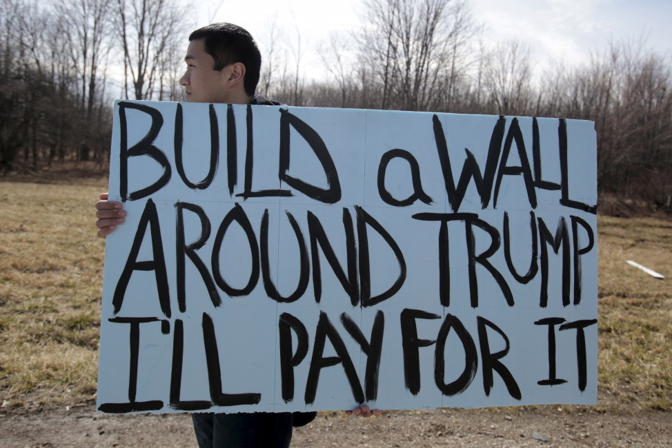 An anti-Trump protester holds his protest sign outside a rally for Republican presidential candidate Donald Trump in Cleveland, Ohio, March 12, 2016. (Reuters)