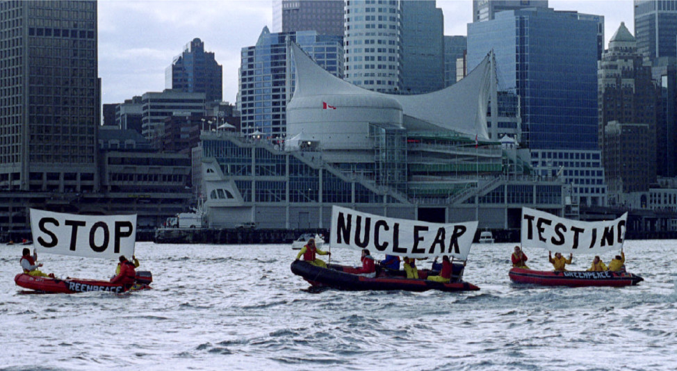 Greenpeace protesters man rubber boats in Burrard Inlet as they protest nuclear testing in the April 1993 file photo in Canada. (Reuters) . In the background with large white sail, is Canada Place, site of Sunday's joint news conference at the close of the summit between US and Russian Presidents -