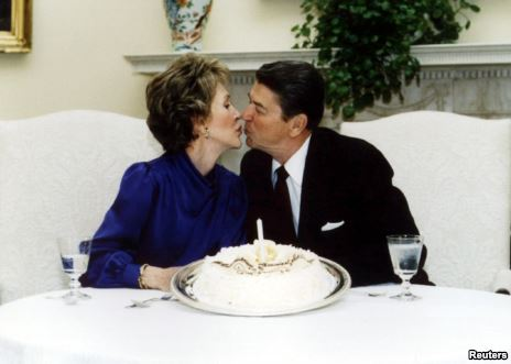 President Ronald Reagan and his wife Nancy kiss on their wedding anniversary in the White House, March 4, 1985.