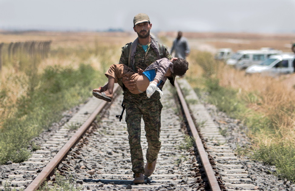 A Kurdish fighter carries a an injured boy in the border in Syrian Tel Abyad town of Raqqa, June 16, 2015. (Reuters)