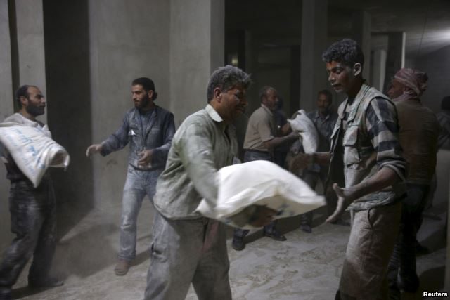 Men store bags of flour unloaded from a Red Crescent aid convoy in the rebel held besieged town of Jesreen, in the eastern Damascus suburb of Ghouta, Syria March 7, 2016 (Reuters)