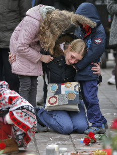 A woman consoles her children at a street memorial after the twin bomb attacks in Brussels on March 23, 2016. (Reuters)