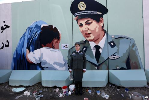 Friba Hameed, 30, an Afghan police officer, poses for a photograph in front of a mural of herself, painted by an independent artist, outside the main gate of a police precinct to mark International Women's Day in Kabul, Afghanistan, March 8, 2016.
