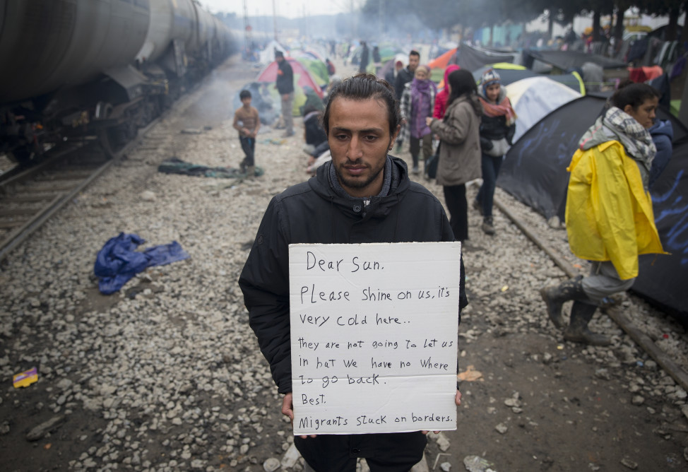 A man holds a banner at a makeshift camp set up near railway tracks at the northern Greek border point of Idomeni on March 16, 2016. (AP)
