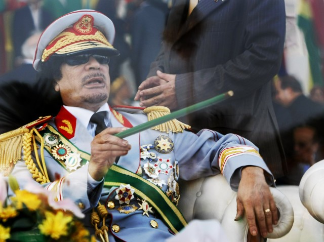 In this Sept. 1, 2009 file photo, Libyan leader Moammar Gadhafi gestures with a green cane as he takes his seat behind bulletproof glass for a military parade in Tripoli. (AP)