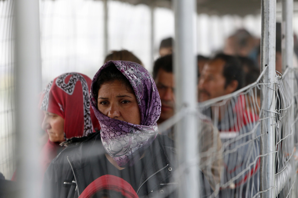 A migrant woman waits in a line to get food at the makeshift camp in the northern Greek border point of Idomeni on April 4, 2016. (AP)