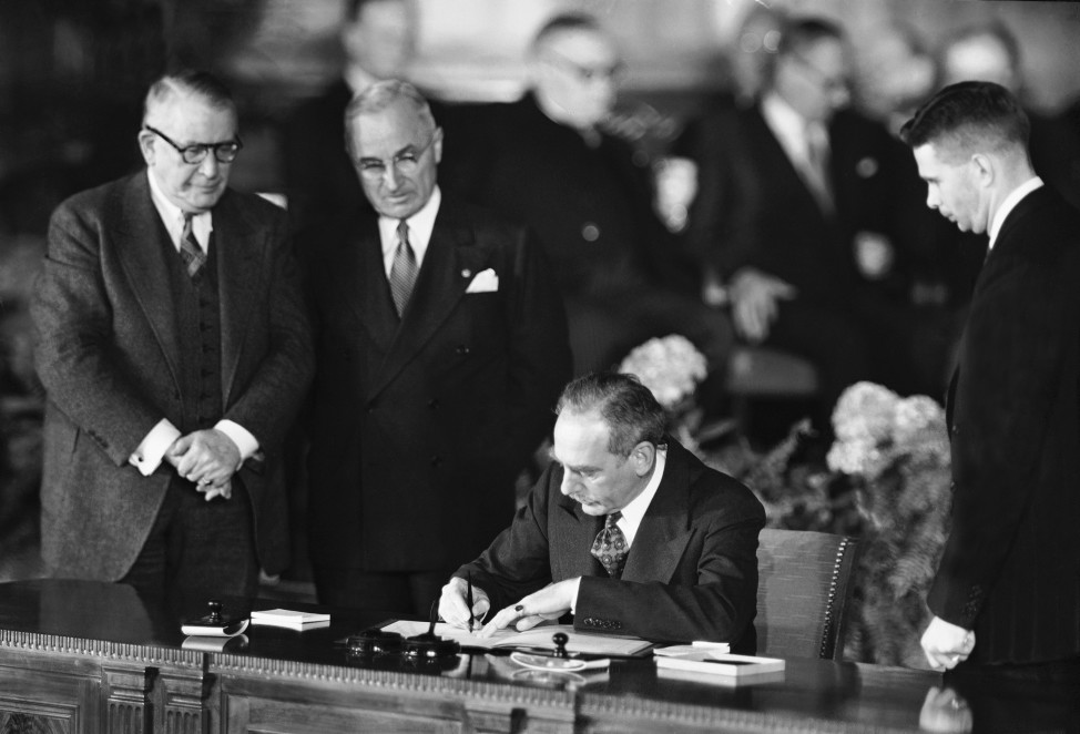 Secretary of State Dean Acheson signs the Atlantic defense treaty for the United States, in Washington on April 4, 1949. (AP file photo)