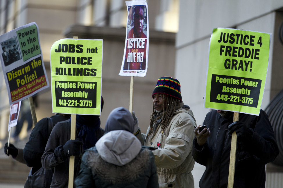 Demonstrators hold up signs outside the courthouse of a trial in connection with the death of Freddie Gray on Jan. 11, 2016, in Baltimore. (AP)