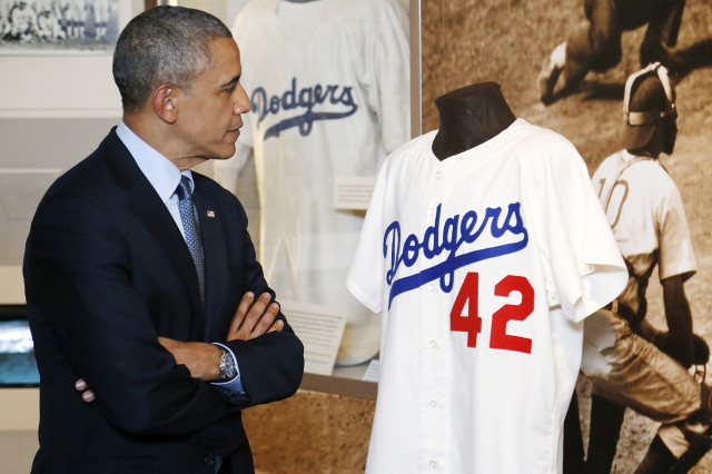 President Barack Obama looks at a Jackie Robinson jersey as he tours the National Baseball Hall of Fame in Cooperstown, New York, May 22, 2014. (Reuters)