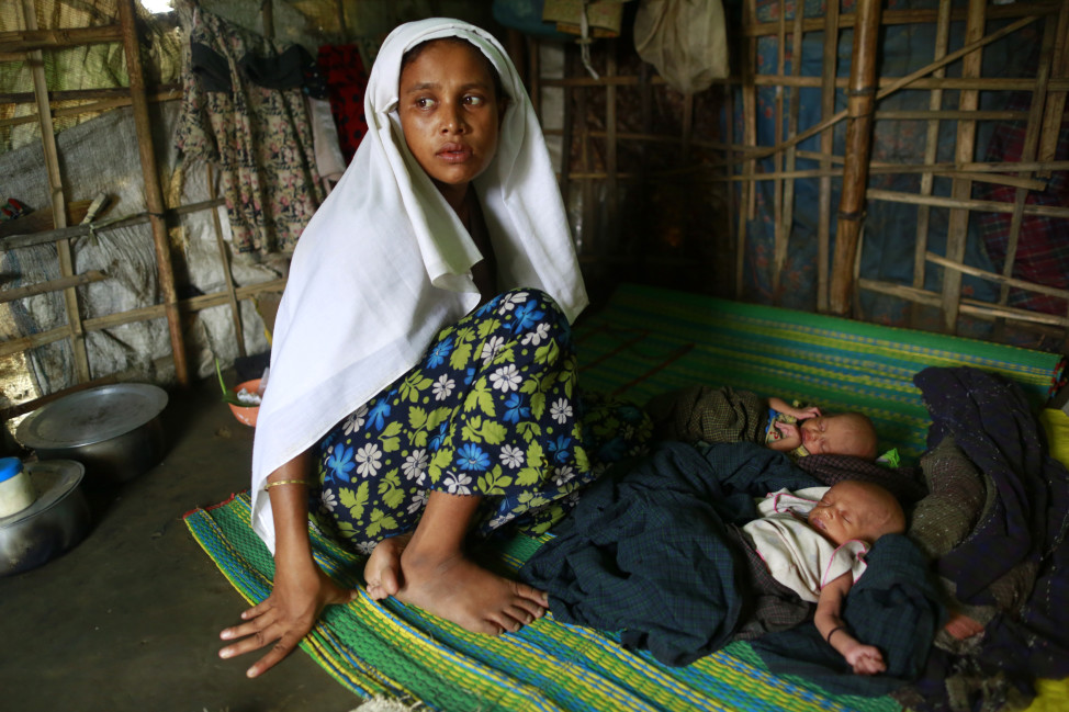 Sinnuyar Baekon, a ohingya Muslims, sits with her twin babies inside her hut at a refugee camp outside Sittwe, the capital city of the Rakhine state June 8, 2014.  (Reuters)