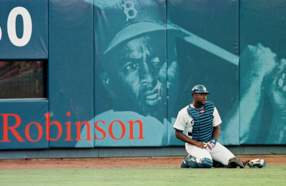 Los Angeles Dodgers catcher Charles Johnson stretches in front of a mural of baseball legend Jackie Robinson at Dodger Stadium before his debut game with the team May 16, 1998. (Reuters)