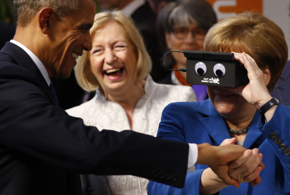 German Chancellor Angela Merkel and President Barack Obama react as they try the virtual reality device PMD in Hanover, Germany on April 25, 2016. (Reuters)