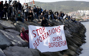 Activists hold a banner as migrants arrive in the Turkish coastal town of Dikili on the first day of an EU brokered deal to deport migrants in Greece on April 4, 2016. (Reuters)