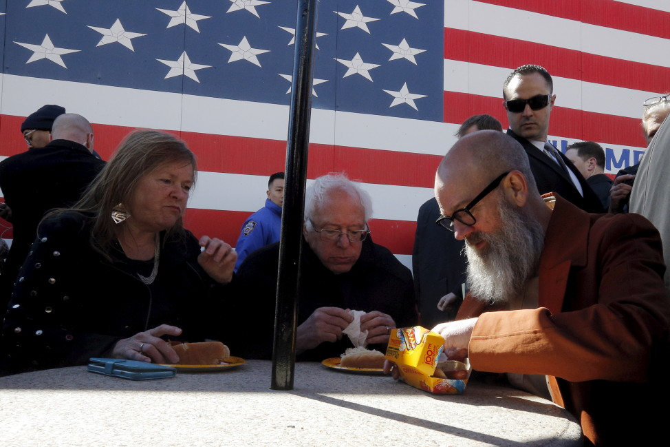 Democratic presidential candidate Senator Bernie Sanders, his wife Jane (L) and musician Michael Stipe eat hot dogs in Coney Island, New York April 10, 2016. (Reuters)