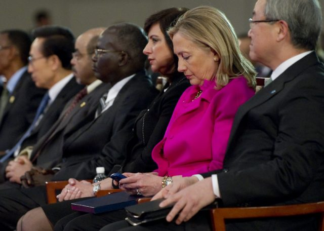 U.S. Secretary of State Hillary Clinton, 2nd right, checks her Blackberry phone alongside South Korean Foreign Minister Kim Sung-hwan, right, as she attends the Fourth High Level Forum on Aid Effectiveness in Busan, South Korea Wednesday, Nov. 30, 2011. (AP)