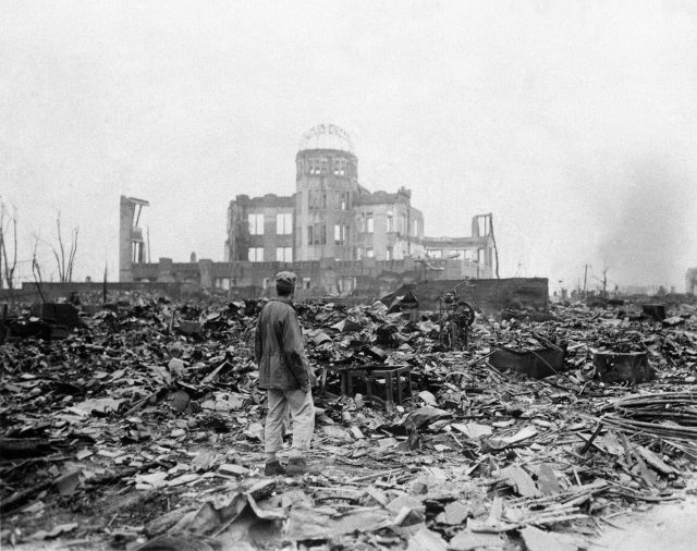 FILE - In this Sept. 8, 1945 file photo, an allied correspondent stands in the rubble in front of the shell of a building that once was a movie theater in Hiroshima, Japan, a month after the first atomic bomb ever used in warfare was dropped by the U.S. on Monday, Aug. 6, 1945. (AP)
