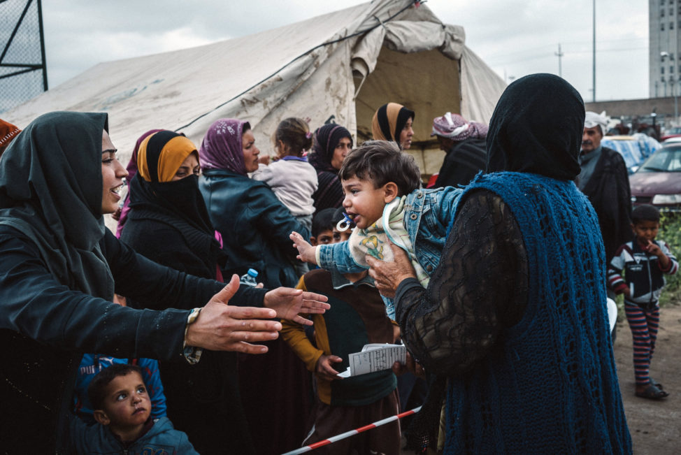 Civilians displaced by heavy fighting between Iraqi security forces and ISIS militants line up outside a tent set up by MSF, or Doctors Without Borders, to provide medical aid, in Makhmour, east of Mosul, Iraq, Monday March 28, 2016. (AP)