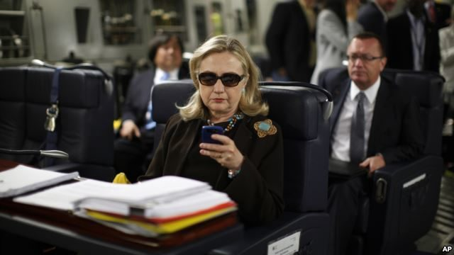 FILE - Then-secretary of state Hillary Clinton checks her BlackBerry from a desk inside a C-17 military plane upon her departure from Malta, in the Mediterranean Sea, bound for Tripoli, Libya, Oct. 18, 2011.